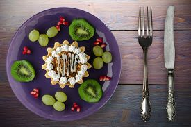 Dessert Of Cake And Fruit Grapes, Kiwi, Pomegranate On A Purple Wooden Background. Dessert On A Purp