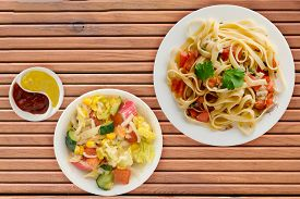 Spaghetti On A White Plate With Vegetarian Salad Top View. Spaghetti Tomatoes, Onions, Cabbage On A