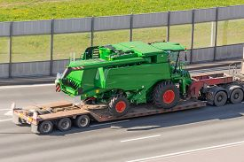 Transportation Of Agricultural Machinery Harvester On A Trailer Of A Truck Loading Platform On A Hig