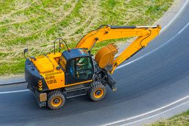 Excavator Travels On The Road To Turning