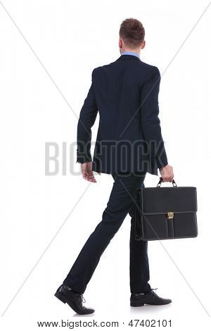 full length back view picture of a young business man with a suitcase in his hand walking away. on white background