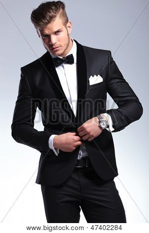 elegant young fashion man in tuxedo buttoning his jacket while looking at you. on gray background