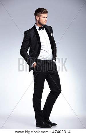 full length picture of an elegant young fashion man in unbuttoned tuxedo with his hands in his pockets and looking away from the camera.on gray background