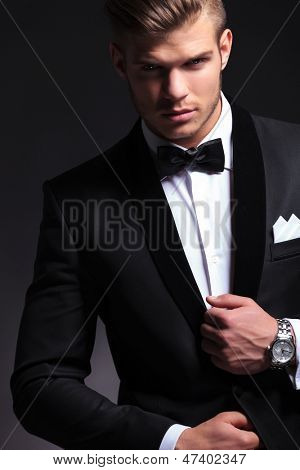 cutout picture of an elegant young fashion man fixing his tuxedo while looking at the camera.on black background