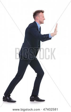 full length picture of a young business man pushing an imaginary wall to a side. on white background