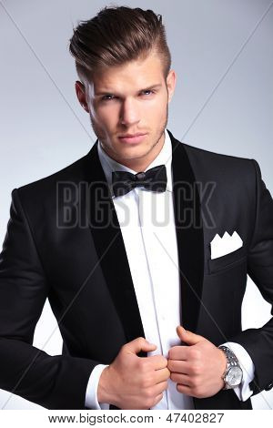 cutout picture of an elegant young fashion man holding both hands on his tuxedo jacket while looking at the camera. on gray background