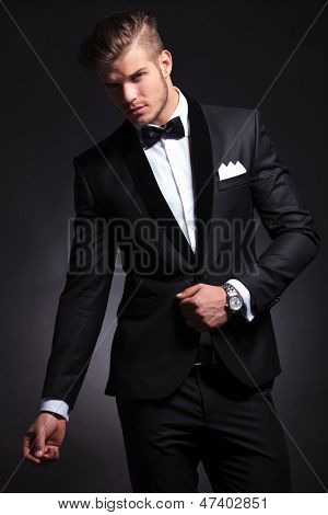elegant young fashion business man posing in his tuxedo while looking at the camera.on black background