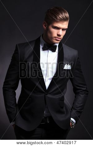 elegant young fashion man in tuxedo holding his hands in his pockets and looking to the camera.on black background