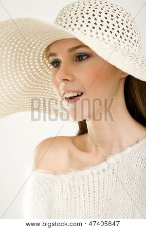 Young beautiful girl in a white hat