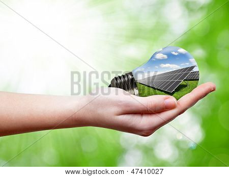 Bulb with of solar panel in hands on green background