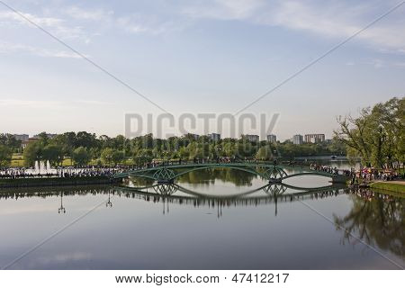 Footbridge Reflecting In The Pond