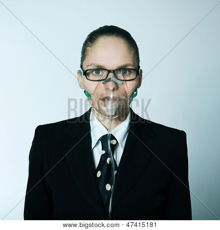 studio shot portrait of one caucasian young breathless business woman  with oxygen mask