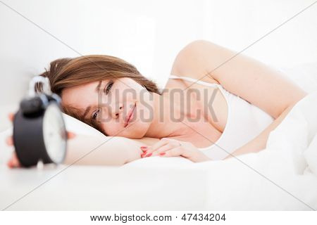Closeup of beautiful woman lying on the bed with alarm clock