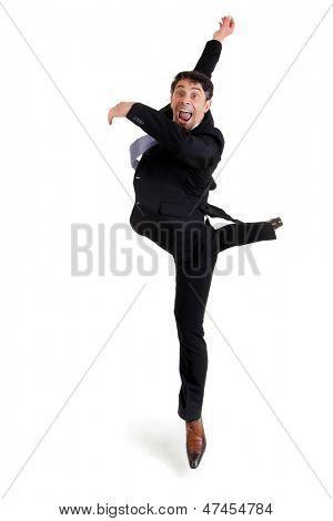 Fun portrait of an excited agile businessman in smart shoes and a suit performing ballet doing a pirouette, isolated on white