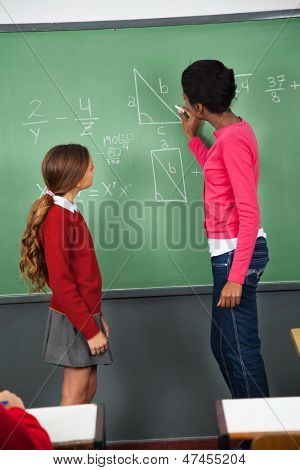 Side view of young female teacher teaching mathematics to teenage schoolgirl in classroom