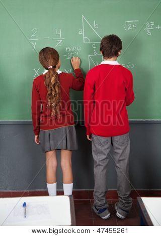 Rear view of teenage schoolchildren writing on board in classroom