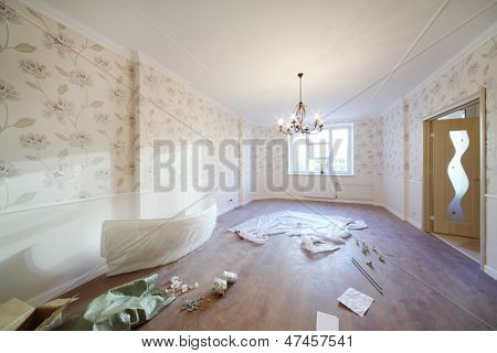 Spacious room with chandelier, window and parts for repair on floor in new apartment.