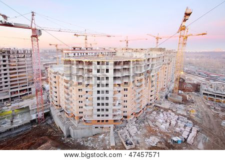 Lots of tower cranes build large residential building at evening.