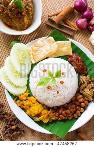 Nasi lemak kukus traditional malaysian spicy rice dish, fresh cooked with hot steam. Served with belacan, ikan bilis, acar, peanuts and cucumber. Decoration setup.