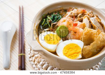 Singapore prawn mee or prawn noodles. Famous Singaporean food spicy fresh cooked har mee in clay pot with hot steam. Asian cuisine.