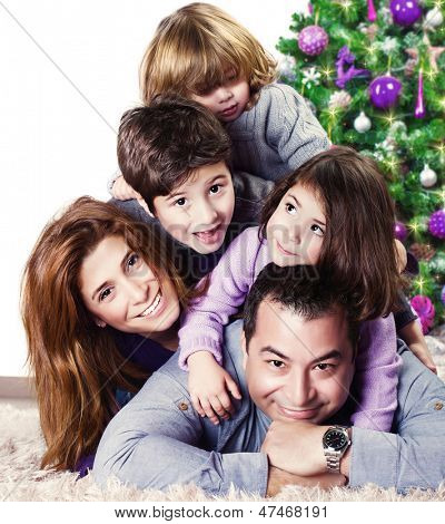 Closeup portrait of cute cheerful family lying down near Christmas tree at home, happy parents with three kids celebrate New Year holiday, love concept