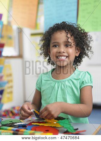 Retrato de menina sorridente montar quebra-cabeças na sala de aula