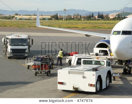 Loading suitcases and other cargo in an airplane on the runway poster