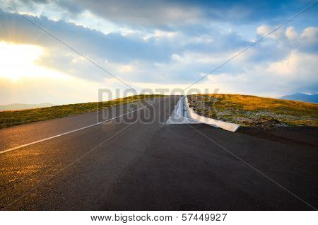 Road over the mountains at sunset with ablue sky and bright sun