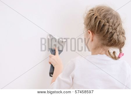 Little Girl Repairs Wall With Spackling Paste. Place For Text.