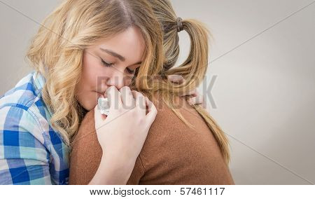 Mother embracing and soothes depressed daughter