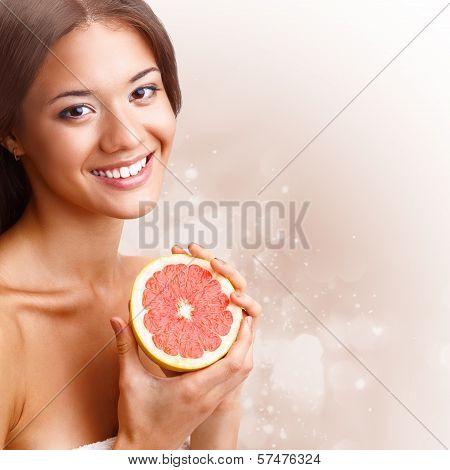 beautiful woman holding half of grapefruit
