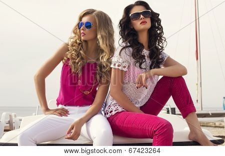 Fashion Photo Of Two Beautiful Girls With glasses Posing On Beach