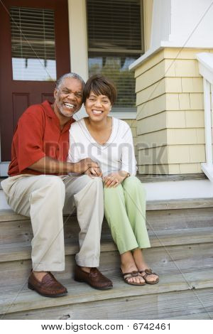 Couple Sitting On Outdoor Steps Of Home Smiling