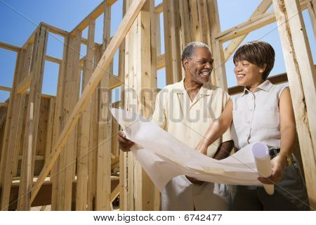 Couple Holding Building Plans On Construction Site