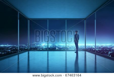 Businessman looking at night city