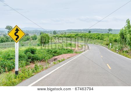 Twisty Road With Roadsign In Nature