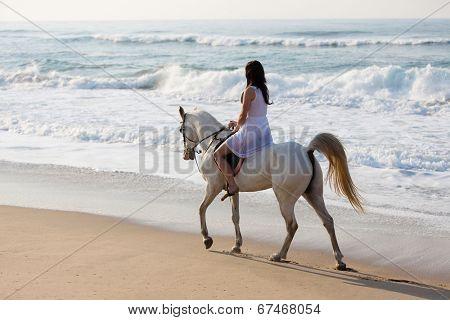 girl in white dress enjoying horse ride on the beach