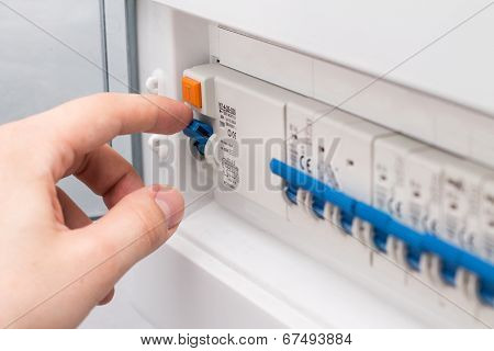 Man turning on the fuse box