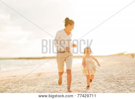 Happy Mother And Baby Girl Running On Beach At The Evening