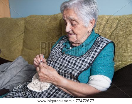Elderly Woman Sewing In Her Home