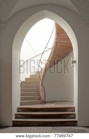 Gothic pointed arch with curved staircase in a historic building poster