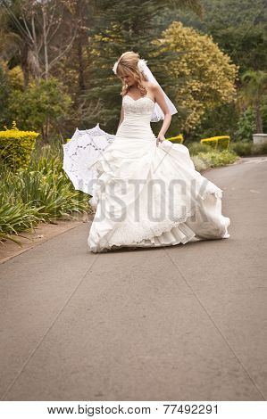 Young beautiful blonde bride enjoying a walk outdoors