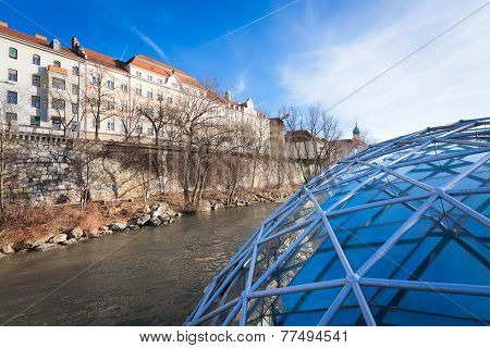 Graz City Seen From Island On Mur River Connected By A Modern Steel And Glass Bridge