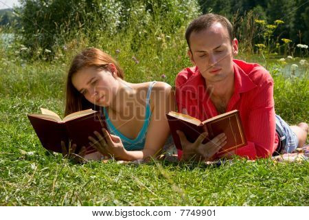Young cople laying on a blanket on the grass on a hot summer day and reading book. Woman and man are enjoying the sunshine in a park. Just happy couple relaxing. poster