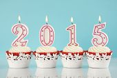 Happy New Year for 2015 red velvet cupcakes in red and white theme with lit candles and pale blue and white background poster