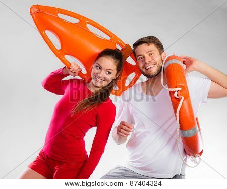 Accident prevention and water rescue. Young man and woman lifeguard couple on duty holding ring buoy float lifesaver equipment having fun on gray poster