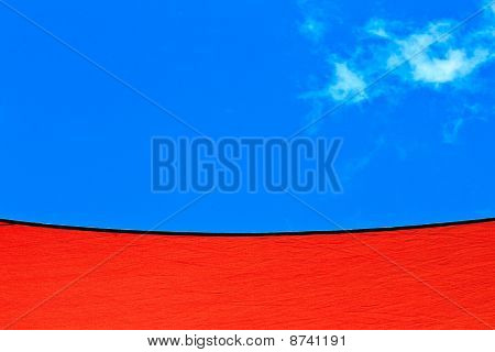 Red canvas sails against a bright blue sky