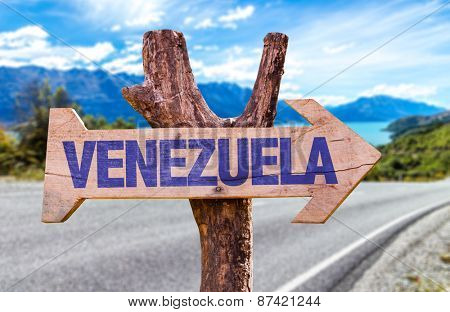 Venezuela wooden sign with road background
