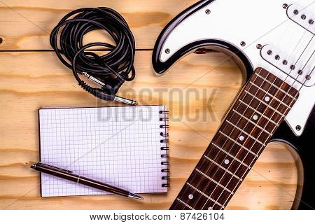 electric guitar and memo pad on wooden table.