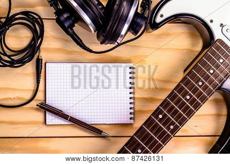 electric guitar, memo pad , and a professional grade headphones